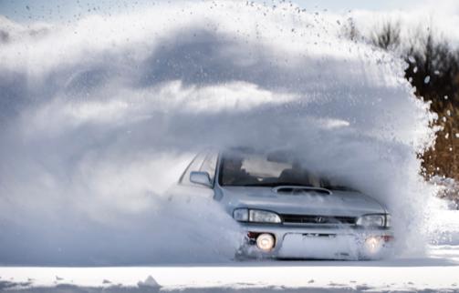 Boetecalculator waarschuwt voor snelheidsovertreding in de sneeuw, zoals deze auto begaat.