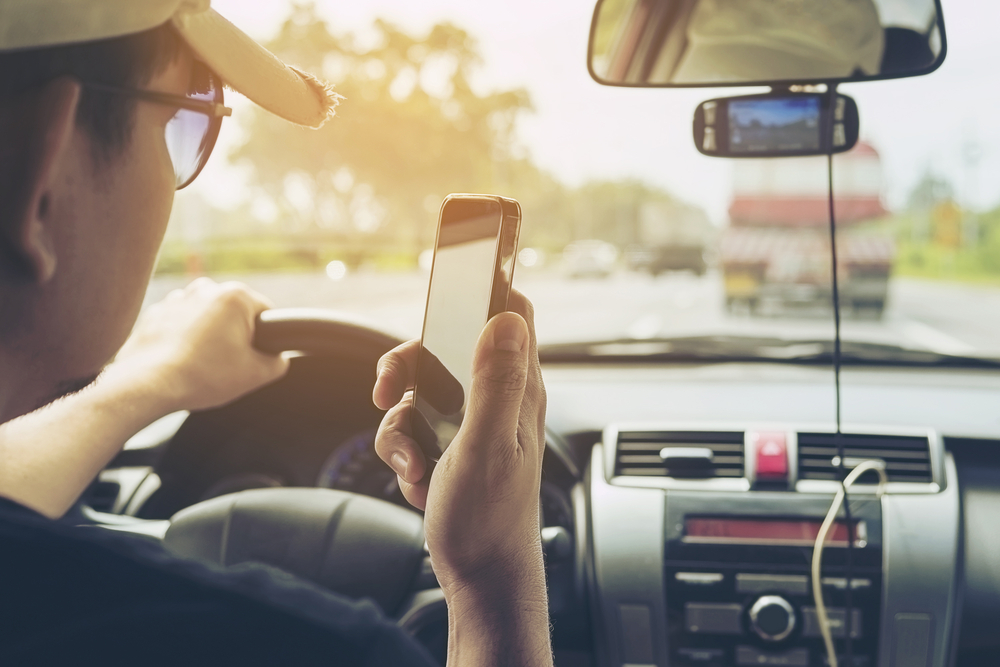 Man is afgeleid door zijn gsm tijdens het rijden en riskeert door het rood licht te rijden. - Boetecalculator