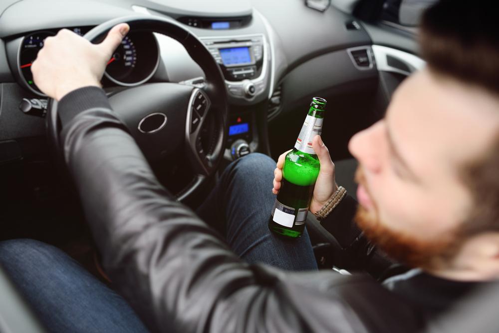Un homme boit de la bière en voiture et risque une amende alcool au volant lors d'un contrôle d'alcoolémie. – Mon Amende