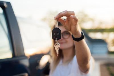 Vrouw toont autosleutel. Boetecalculator waarschuwt voor extra alcoholcontroles deze zomer.
