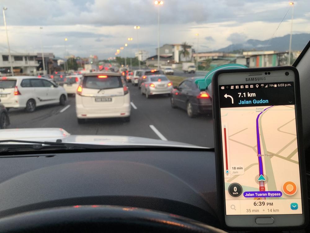 Smartphone in auto met app die files weergeeft. Boetecalculator over de verkeersovertreding van de filerat.