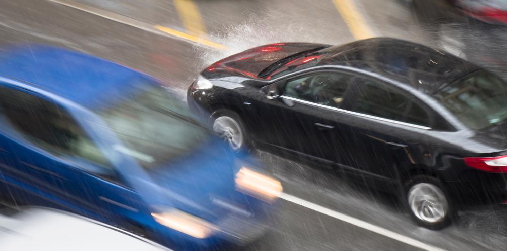 auto's kruisen elkaar in de regen. Vermijd snelheidsovertredingen bij slecht weer. Boetecalculator.