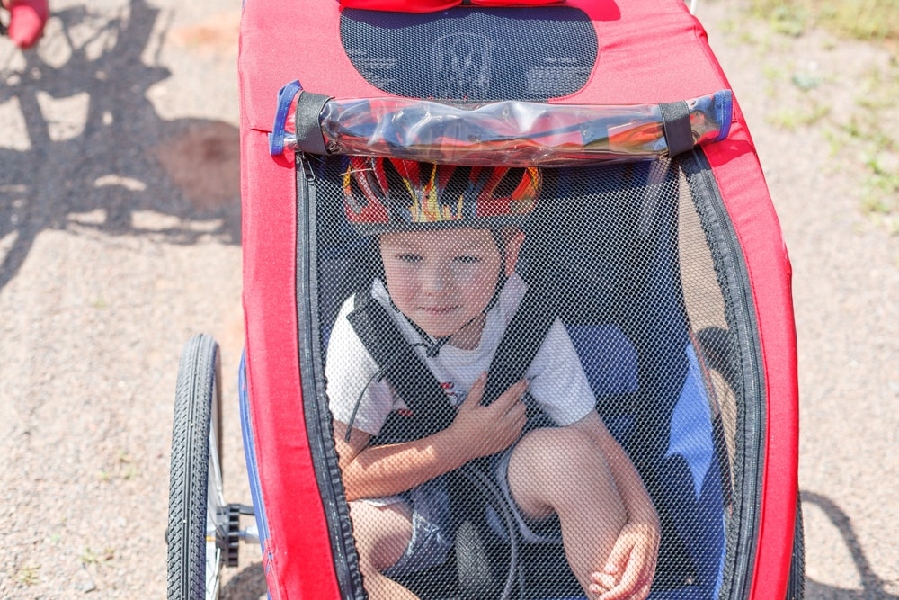 Jongetje zit met helm op in een rode fietskar - Boetecalculator