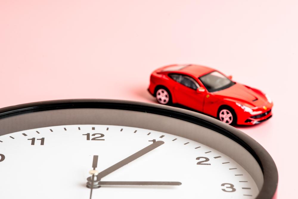 Petite voiture à côté d'une horloge. Mon Amende concernant les infractions routières et accidents pendant l'heure d'hiver.