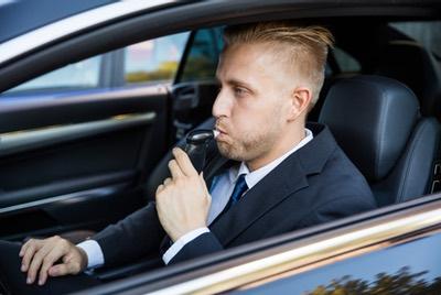 Homme en voiture souffle dans appareil. Mon amende fait le point sur vos droits lors de contrôles d'alcoolémie.