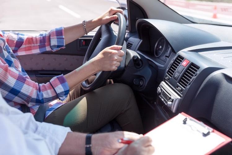 Examinator en leerling samen in auto. Voortaan ook simulatie rijden onder invloed tijdens terugkommoment. – Boetecalculator