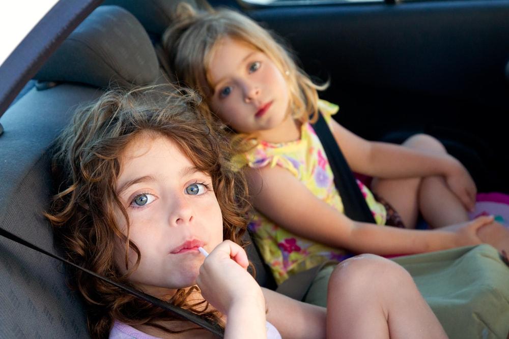 twee meisjes zitten achteraan in de auto met de gordel aan - Boetecalculator