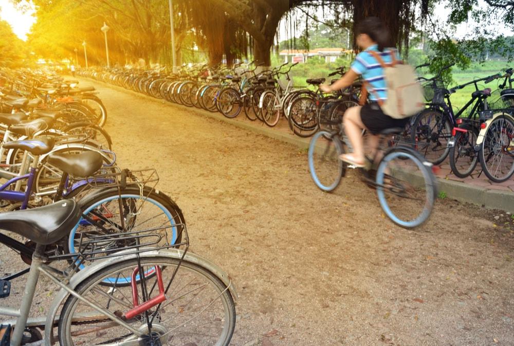 Meisje rijdt met de fiets en rondom haar staan allemaal fietsen gestald - Boetecalculator